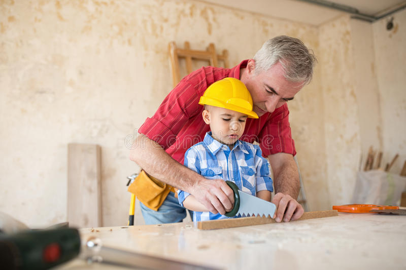 Working fun grandfather and grandson in a carpenter`s workshop stock images