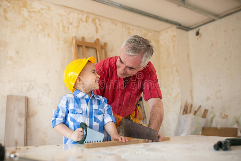 Working fun grandfather and grandson in a carpenter`s workshop stock photo