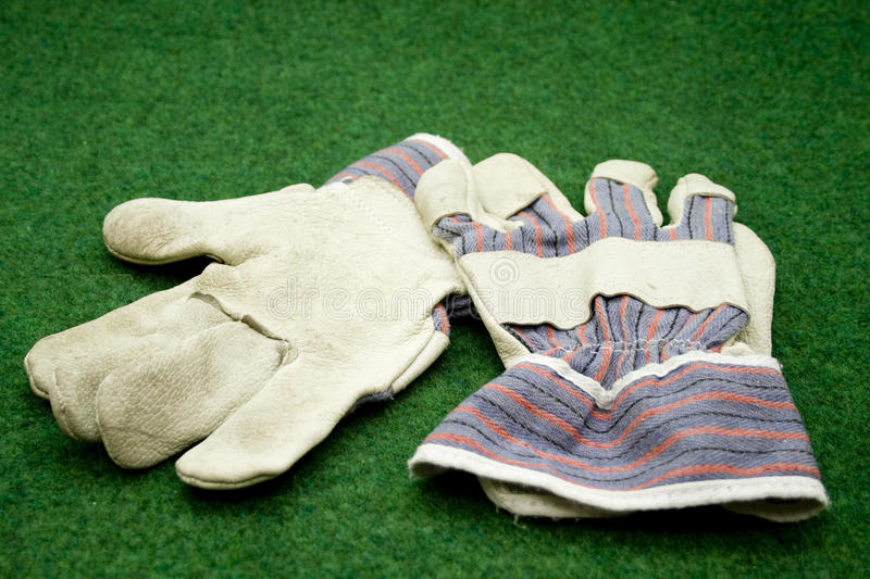 Working gloves. On green mat royalty free stock photo