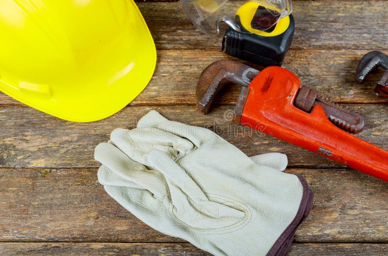 Working gloves, building helmet and glasses, tool equipment on wood table royalty free stock images