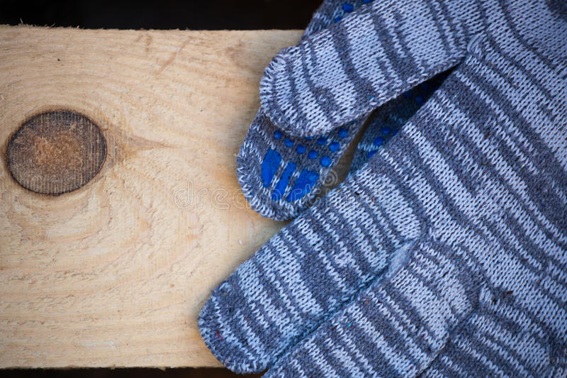 Working gloves on Industrial wood. With knot royalty free stock image