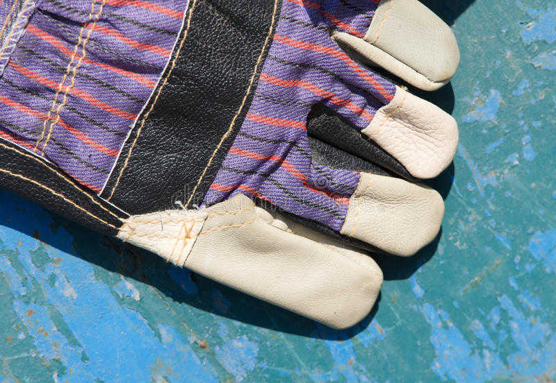Working gloves. New protective gloves on blue board stock photo
