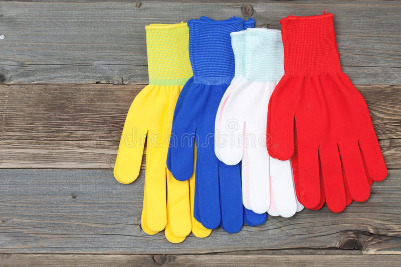Working gloves on old boards. New varicolored working gloves over old wooden table, construction tools stock image