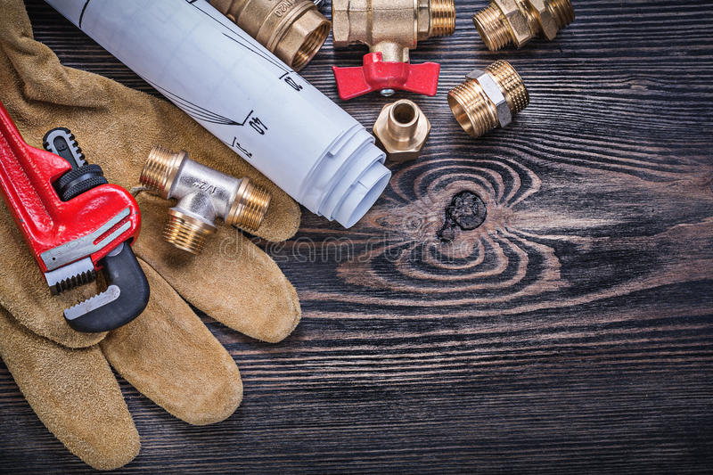 Working gloves pipe wrench engineering drawings brass plumbing f. Ittings water gate valve on wooden board royalty free stock photos