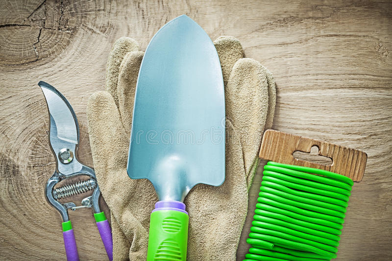 Working gloves secateurs hand spade soft wire tie on wooden boar. D gardening concept stock images