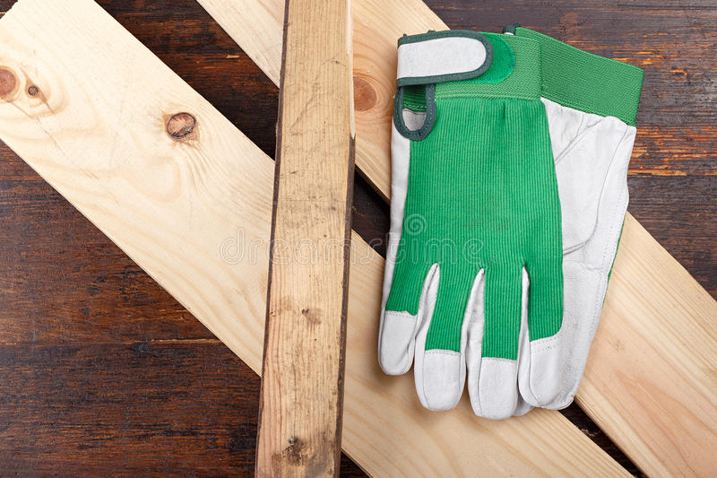 Working gloves on a wooden background. Working gloves lie on a log, on a wooden background. The beginning of the carpenter& x27;s work royalty free stock image