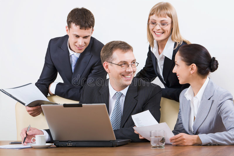 Working in a group. Group of four young businesspeople discussing different questions holding documents gathered together around the table with the laptop