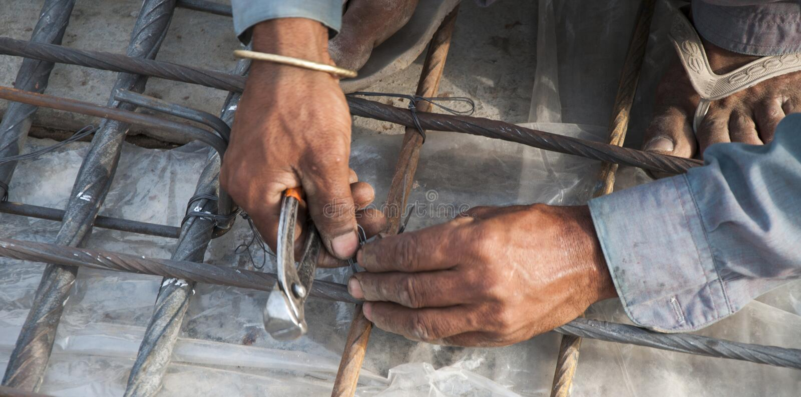 The working hands on steel-fixing. A steel fixer is working on the roof stock photos