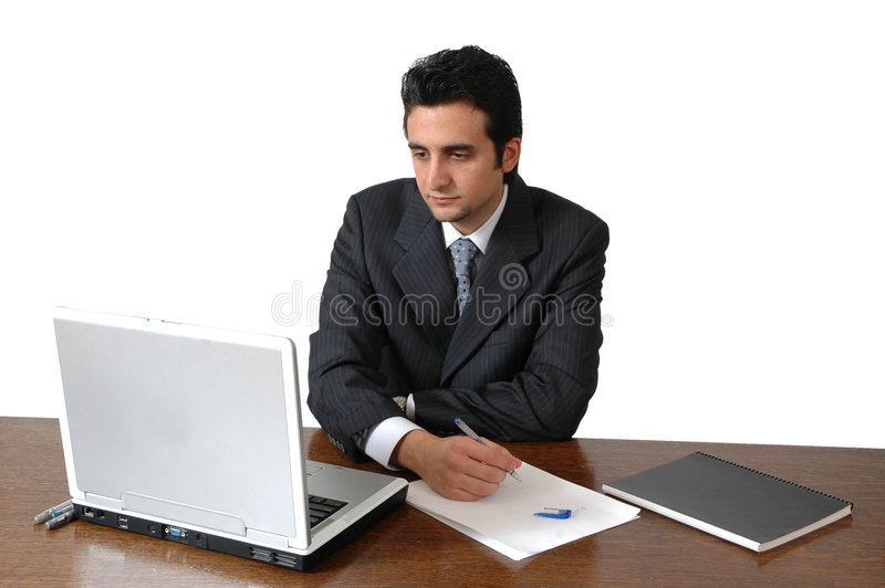 Working Hard. A middle eastern man works on his laptop at his desk. Man isolated on white background. Man with business suit and tie in an office setting stock photography