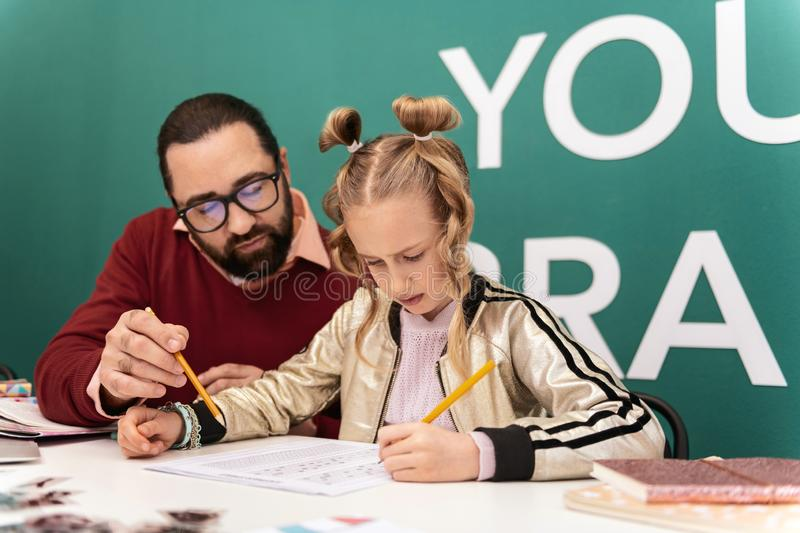 Dark-haired bearded adult teacher in eyewear and his pupil looking concentrated royalty free stock photos