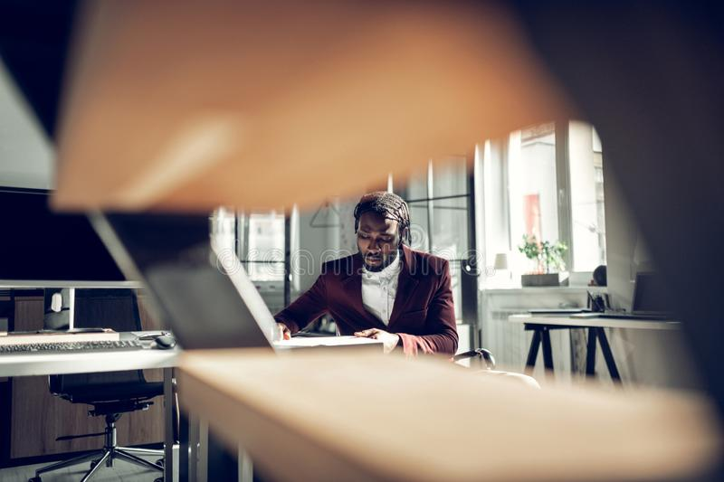 Handsome dark-skinned businessman working in the office royalty free stock photography