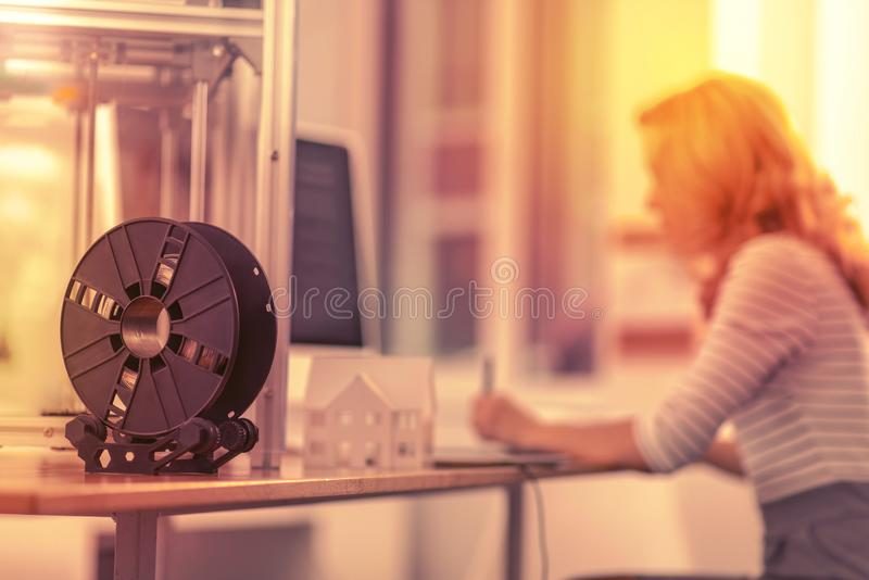 Focused reliable woman being engrossed in her work in the background. stock image