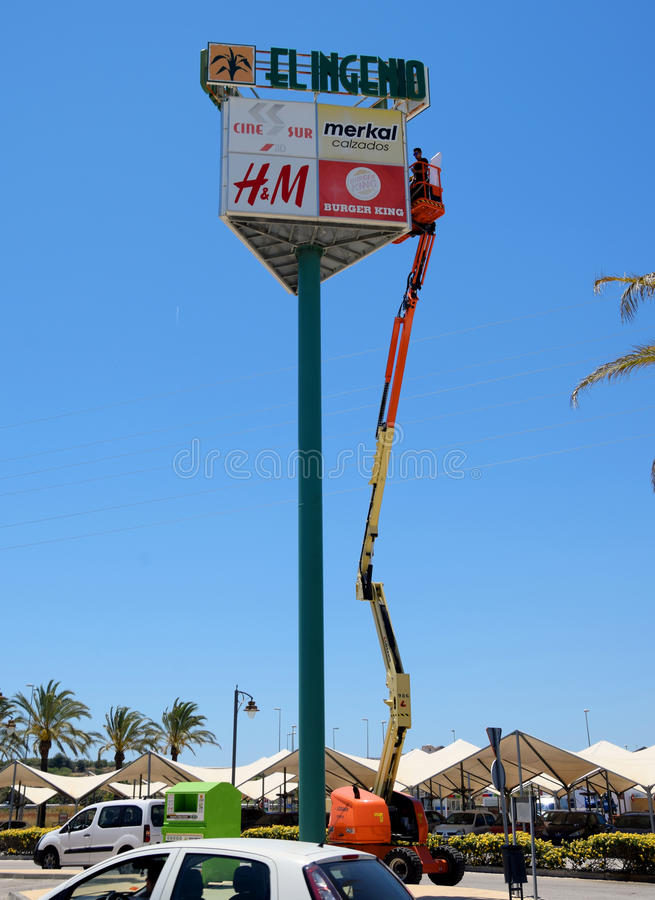 Man working at height to replace signs. A man, works high up, at the top of a hydraulic arm, replacing advertising boards at a Spanish shopping centre car park royalty free stock photos