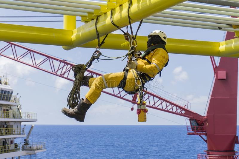 Offshore services. Working at height. Working overboard. A commercial abseiler with fall arrestor device hanging on bridge pipeline structure at oil and gas royalty free stock image