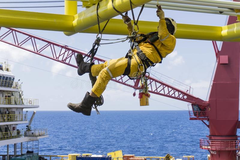 Offshore services. Working at height. Working overboard. A commercial abseiler with fall arrestor device hanging on bridge pipeline structure at oil and gas royalty free stock photography
