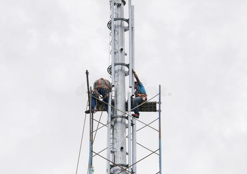 Working at height. SELANGOR, MALAYSIA - MAY 21, 2016: Riggers are working at top of the monopole for installing scaffolding before radio frequency antenna and royalty free stock images