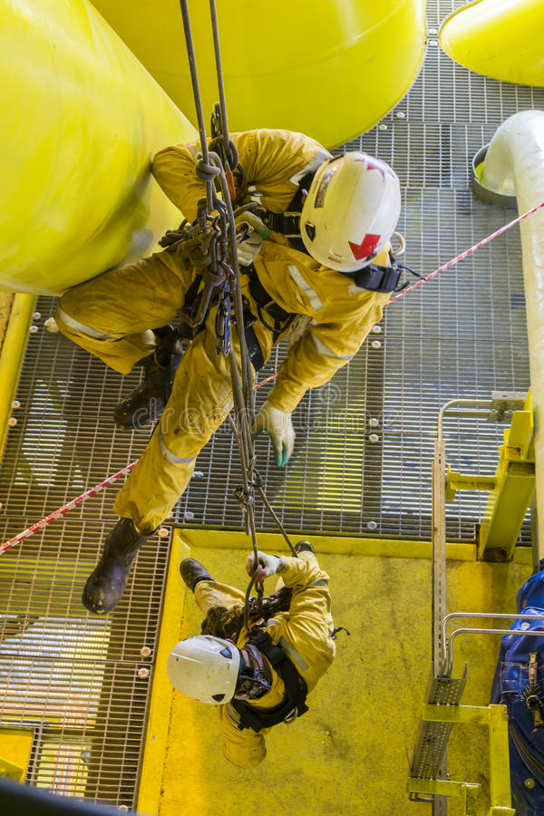 Oil and gas industrial occupational. Working at height. Two abseilers hanging at oil and gas platform for equiment inspection stock images