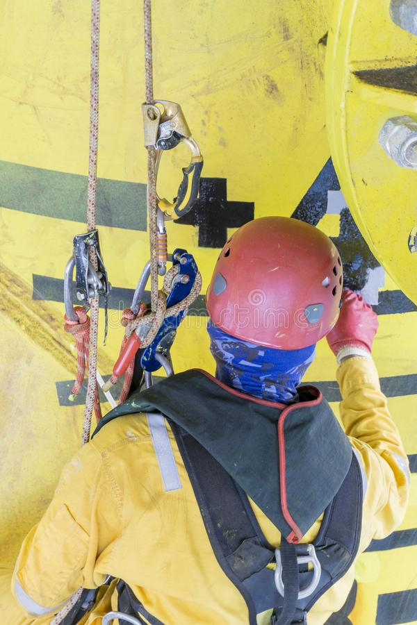 Industrial Occupation. Working at height. Working overboard. A commercial abseiler with fall arrestor device perform painting works on oil and gas jacket stock images