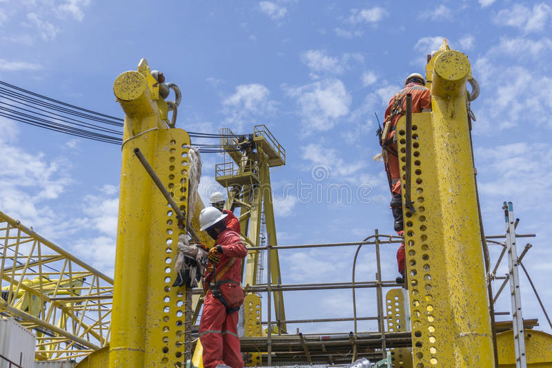 Working at heights. Offshore workers complete with falling protection working at height royalty free stock photography