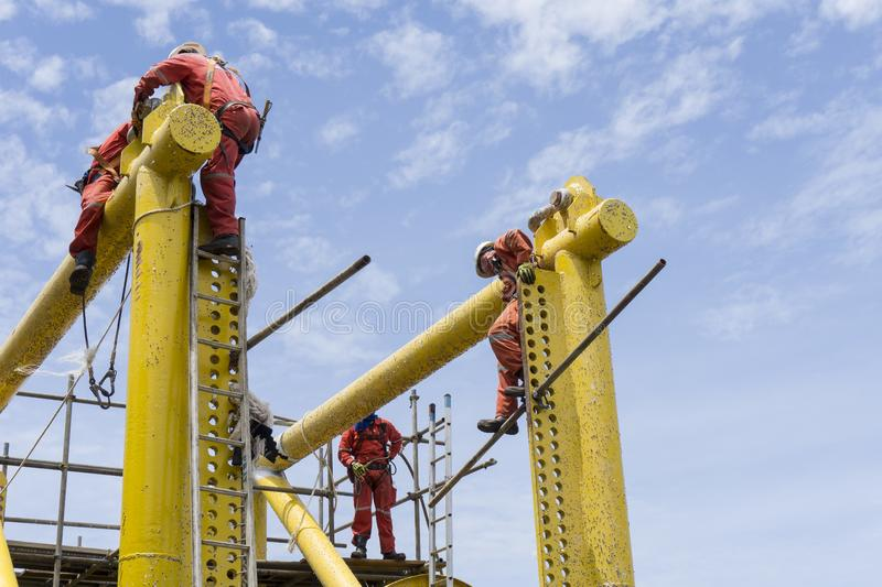 Working at heights. Offshore workers complete with falling protection working at height royalty free stock photo