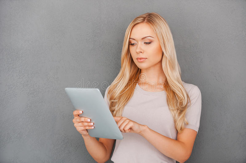 Working on her brand new tablet. stock image