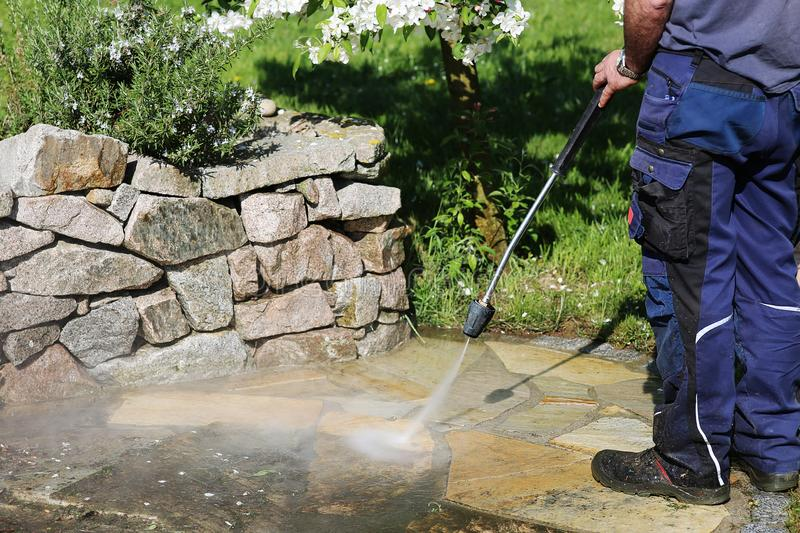 Working with high-pressure cleaner. Janitorial service, cleaning of stones in the garden with the high-pressure cleaner stock photo