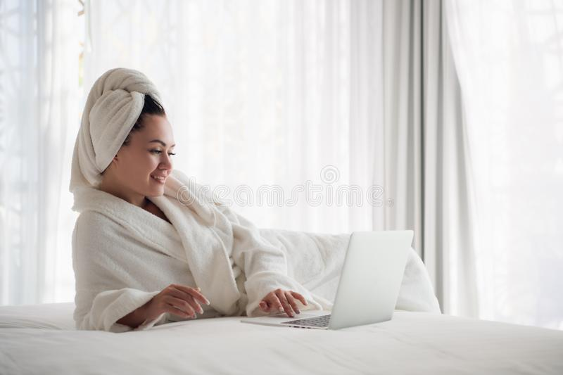 Working at home concept. Girl is working on her laptop in bed. Relaxing working process. royalty free stock images