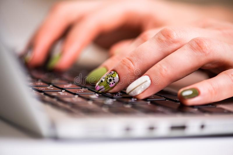 Working at home with laptop woman writing a beauty blog. Female hands with bright manicure on the laptop keyboard stock photo