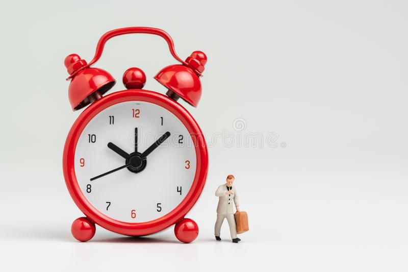 Working hours, time to go to work or meeting schedule concept, miniature figure businessman looking at his watch holding suitcase. Walking with big red alarm stock images