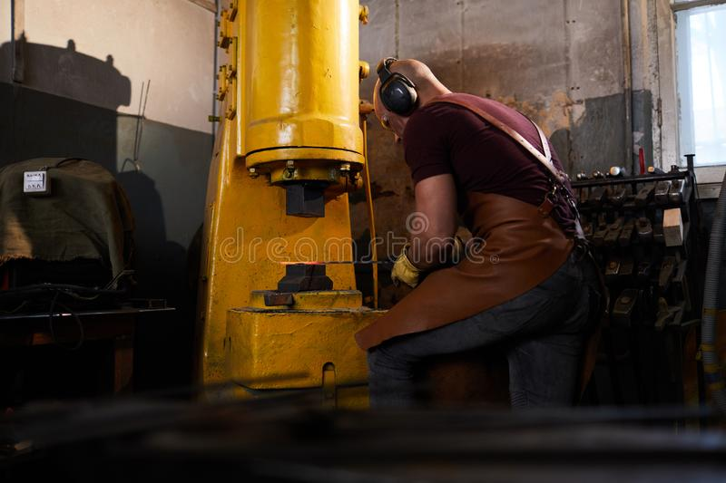 Working with hydraulic forging press. Concentrated skilled man in apron and ear protectors putting metal bar under press while working with hydraulic forging royalty free stock photography