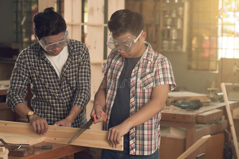 Working in joinery. Asian father and son working in joinery together royalty free stock image