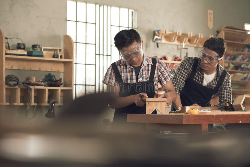 Working in joinery. Father looking how his son working with wood in joinery stock image