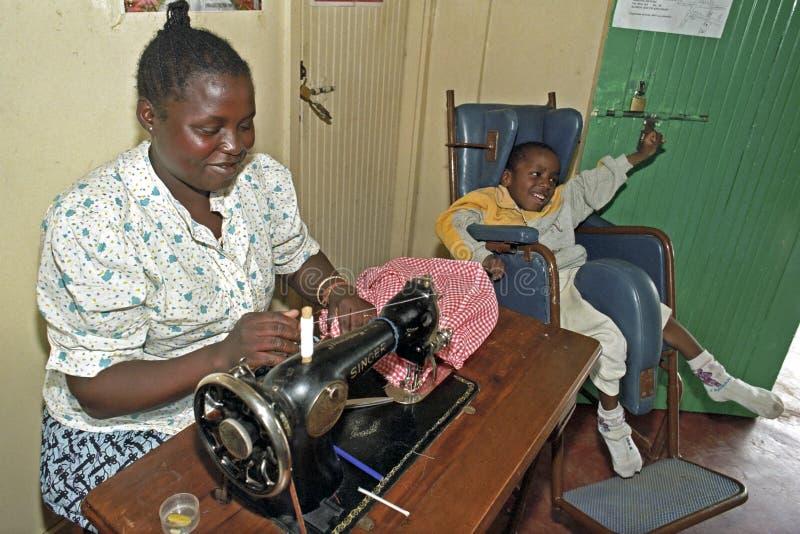 Working Kenyan woman with disabled child, Nairobi. Kenya, capital, city Nairobi: in the Mukuru kwa Njenga slum in a working mother in a sewing workshop with her royalty free stock image