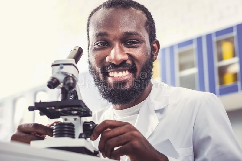 Beginning microbiologist smiling working in lab. Working in lab. Beginning skillful microbiologist smiling while working in modern spacious lab royalty free stock photos