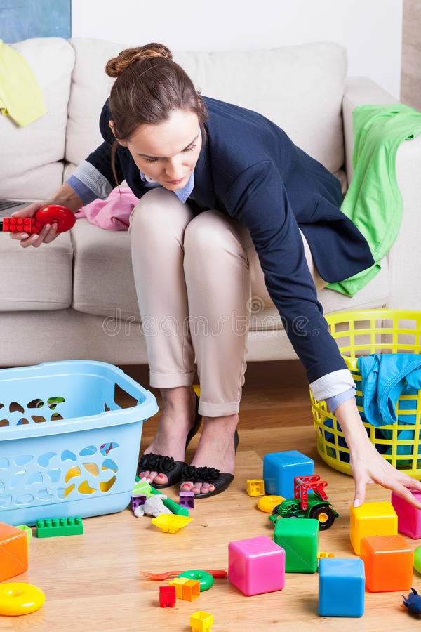 Working lady cleaning up toys. Working lady cleaning up colorful kids toys stock photos