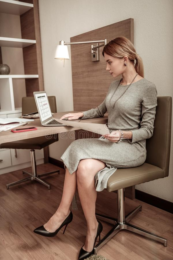 Blonde-haired woman wearing dress and accessories working on laptop royalty free stock image