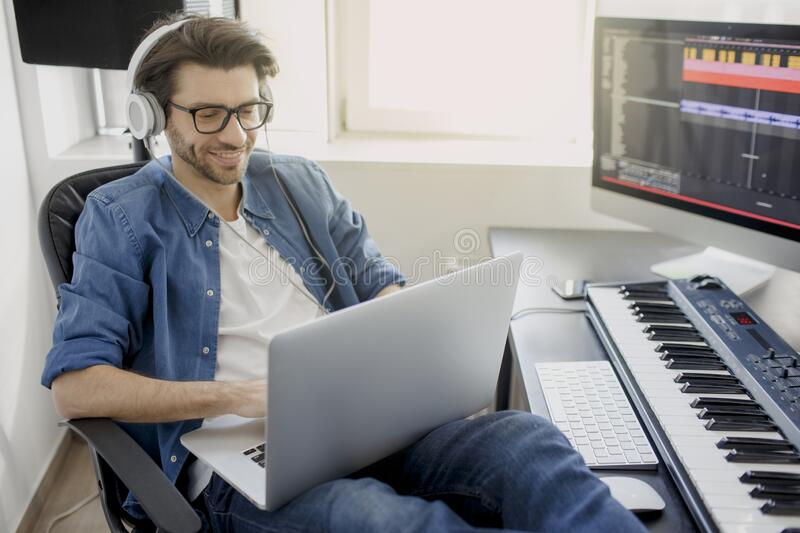 Working on a laptop. Busy guy. Multitasking concept. DJ in broadcasting studio. music producer is composing a song on. Synthesizer keyboard and computer in stock photography
