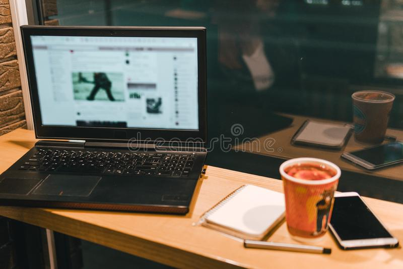 Working on laptop in cafe, smartphone, pen, use computer. Freelancer works remotely. Online marketing, education for adulte. Night stock photography
