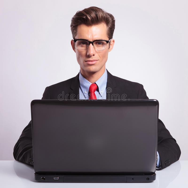 Working on laptop at desk. Young business man working on a laptop at the desk and looking at the camera, on gray background stock image