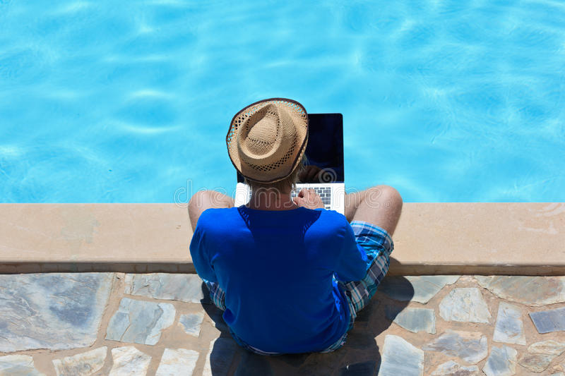Working on laptop at the pool stock photography