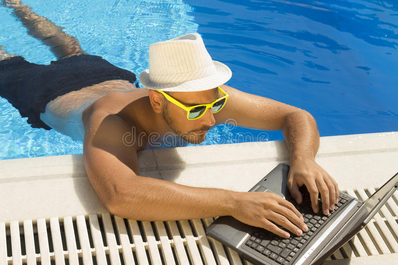Working on laptop from the swimming pool. stock images