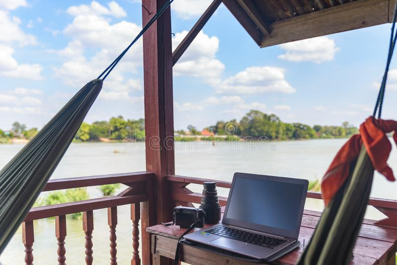 Working with laptop on wooden balcony in tourist resort with hanging hammock on the Mekong River, Laos. Concept of millenials stock photos