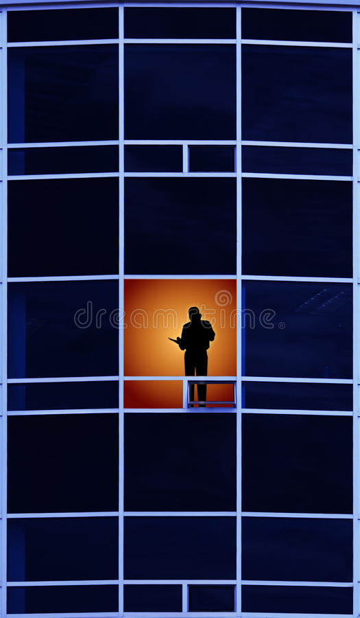 Working late. Man in modern office building using his cellphone and looking out the window working late royalty free illustration
