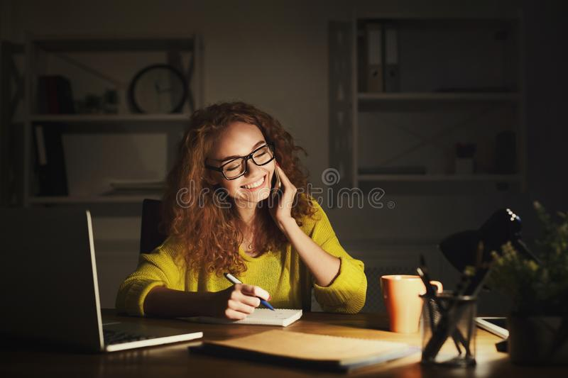 Smiling woman at work talking on phone royalty free stock photography