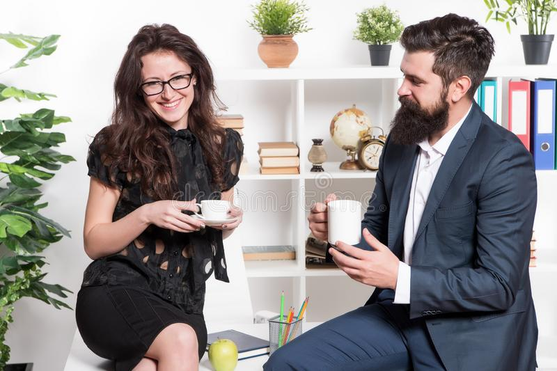 A working lunch meeting. Colleagues talking during work lunch. Sexy woman and bearded man enjoying lunch break in office stock photography