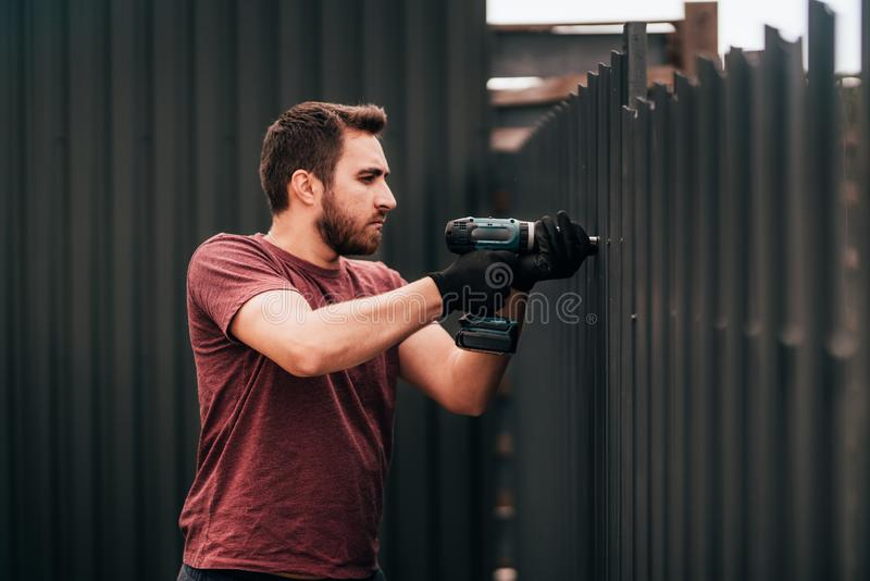 Working man portrait - construction worker using screwdriver and installing elements royalty free stock photo