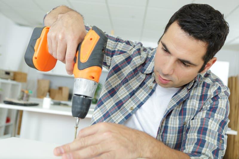 Working man practising skills in making drawer at workshop royalty free stock photography