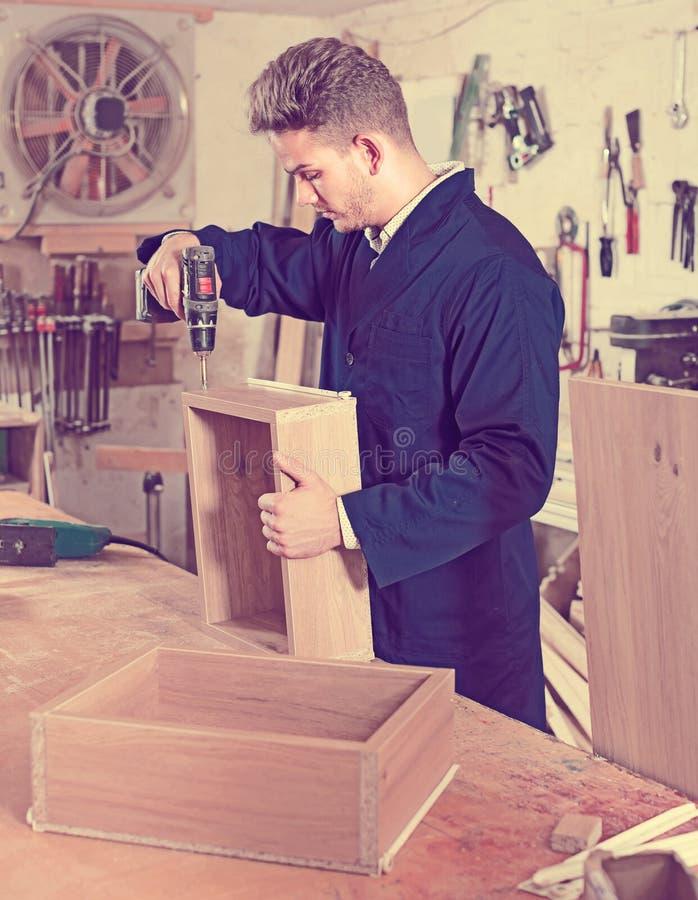 Working man practising his skills in making drawer at workshop stock image