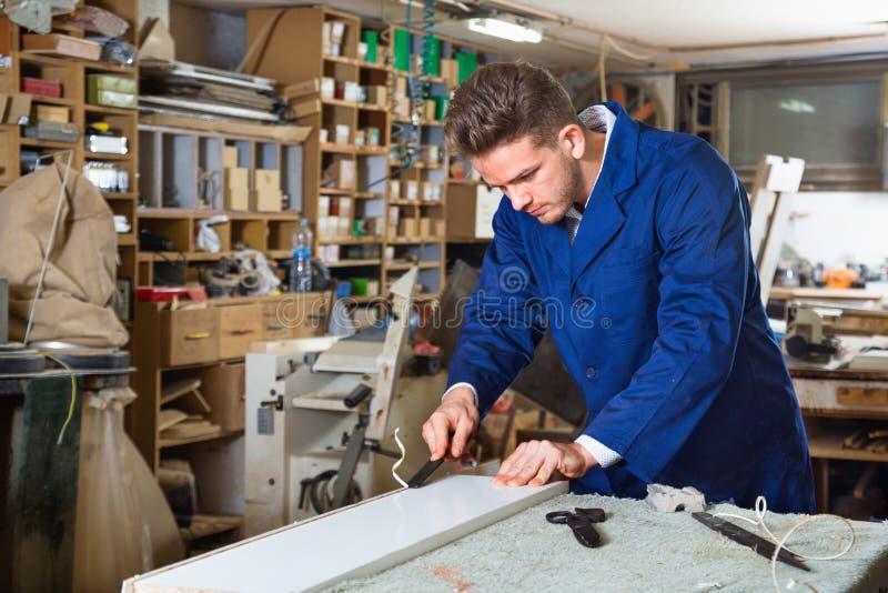 Working man practising his skills in plank chiseling. Smiling diligent working man practising his skills in plank chiseling at workshop stock images
