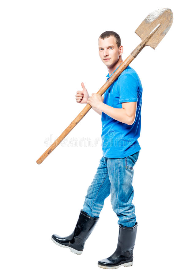 Working man with a shovel goes to dig on a white stock photos